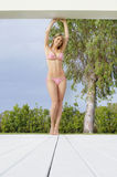 Beautiful Woman In Bikini Standing With Hands Raised In Resort Royalty Free Stock Images