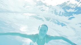 Beautiful woman in bikini swiming underwater in swimming pool. She smiles and looking relaxed and happy. Close up view stock footage