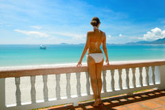 Beautiful woman in bikini on the terrace admiring the sea. Royalty Free Stock Photo