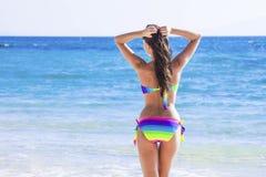 Woman in bikini walking to sea. Beautiful woman in bikini walking to blue tropical sea Royalty Free Stock Image