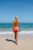 Beautiful woman in bikini walking towards the sea. Rear view of beautiful woman in bikini walking towards the sea. Young female in swimsuit walking on the beach Stock Photo
