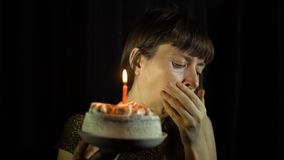 A woman coughing then blowing out a candle on a cake on a black background. Beautiful woman during birthday anniversary wedding celebration looking at the self stock video