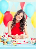 Beautiful woman with a birthday cake hiding her age Royalty Free Stock Image