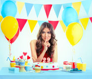 Beautiful woman with a birthday cake making silence gesture Royalty Free Stock Photo