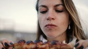 Beautiful woman biting huge pieces of meat eating with hands angry inappropriate in close up view. Beautiful young greedy woman biting huge pieces of meat eating stock footage
