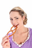 Beautiful woman biting a pretzel. Beautiful blonde woman wearing a Bavarian style purple blouse biting a pretzel with a lovely smile isolated on white Royalty Free Stock Photography