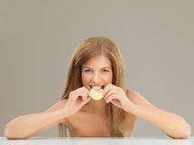 Beautiful woman biting slice of lemon smiling Stock Photos