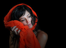 Beautiful woman on black background. Beautiful brunette fashion model on black background with a scarf wrapped around her face Stock Photos
