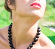 Beautiful woman with black beads made of fresh black currant Stock Photo