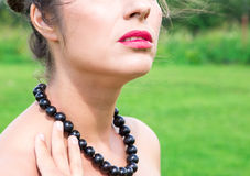 Beautiful woman with black beads made of fresh black currant Royalty Free Stock Photo