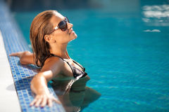 Beautiful woman in black bikini relaxing in the swimming pool Royalty Free Stock Image