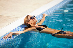 Beautiful woman in black bikini relaxing in the swimming pool Stock Photography