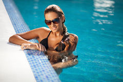 Beautiful woman in black bikini relaxing in the swimming pool Stock Images