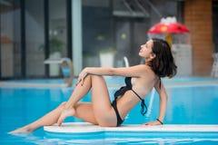 Beautiful woman in black bikini sitting near the swimming pool on resort vacation with blurred background Stock Photos