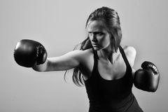Beautiful woman with the black boxing gloves Stock Image