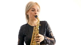 Beautiful woman in black concert dress playing a melody on saxophone melody isolated over white background stock video