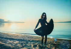 Beautiful woman in black dress on beach. Beautiful fashionable young woman in black dress on beach outdoors Stock Images