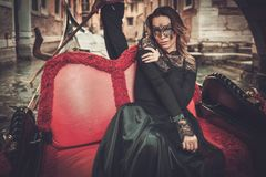 Beautiful woman in black dress with carnaval mask riding on gondola. Royalty Free Stock Photography