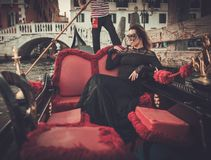 Beautiful woman in black dress with carnaval mask riding on gondola. Royalty Free Stock Image