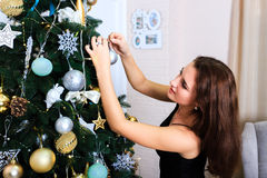 Beautiful woman in a black dress decorates Christmas tree Stock Photography