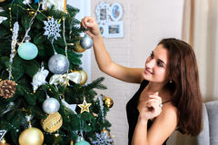 Beautiful woman in a black dress decorates Christmas tree Stock Image