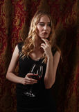 Beautiful woman in black dress with glass of red wine Royalty Free Stock Images