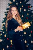 A beautiful woman in a black dress with a Golden gift box stands near the Christmas tree stock images