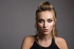 Beautiful woman in black dress. Hairstyle and bright make-up. Stock Image
