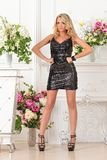 Beautiful  woman in black  dress in luxury studio. Beautiful blonde woman in black shinning dress. Luxury studio with flowers Royalty Free Stock Photography