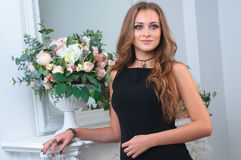 Beautiful woman in a black dress near mirror and the flowers in Stock Image