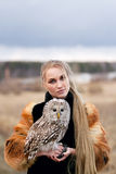 Beautiful woman in a black dress with an owl on his arm. Blonde with long hair in nature holding a owl. Romantic delicate girl Royalty Free Stock Photo