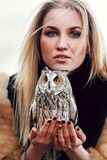 Beautiful woman in a black dress with an owl on his arm. Blonde with long hair in nature holding a owl. Romantic delicate girl Stock Photography
