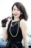 Beautiful woman in black dress and pearl necklace. Young beautiful woman in sixties style in black dress and pearl necklace on the road trip stock photo
