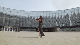 Beautiful woman in black dress playing violin near glass building. Art concept stock footage