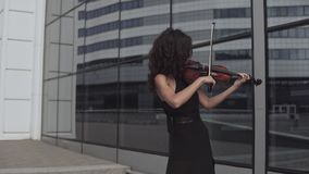 Beautiful woman in black dress playing violin near glass building. Art concept stock video