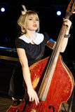 Beautiful woman in black dress plays old contrabass Stock Image