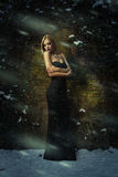 Beautiful woman in a black dress posing in front of a wall on t Stock Image