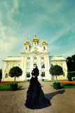 Beautiful woman in black dress posing next to the palace. Royalty Free Stock Photo