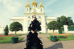 Beautiful woman in black dress posing next to the palace. Royalty Free Stock Photography