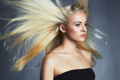 Beautiful woman in black dress. Sexy blond girl.healthy hair.Beauty salon. Flying hair Royalty Free Stock Photos