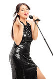 Beautiful woman in black dress singing on microphone Royalty Free Stock Images