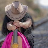 Beautiful woman in a black dress on the train tracks with a pink shawl, a brown hat and a guitar. On an autumn day with blurred background stock photography