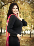 Beautiful woman in black dress in yellow city park, fall season Stock Images