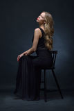 Beautiful woman in a black evening dress posing with chair Royalty Free Stock Images