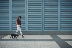 Beautiful woman with black french bulldog puppy at the street Stock Photos