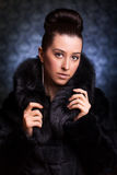 Beautiful Woman in black Fur Coat on the blue Stock Photos