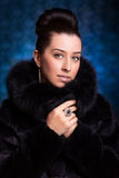 Beautiful Woman in black Fur Coat on the blue Stock Images