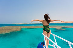 Beautiful woman in black-green swimsuit standing on the nose of. The yacht and spreading hands apart at a sunny summer day, breeze developing hair, beautiful Royalty Free Stock Image