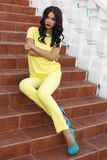 Beautiful woman with black hair in elegant yellow suit Royalty Free Stock Photography