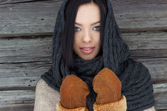 Beautiful woman with black hair in mittens stands near the wooden wall in winter Stock Photography